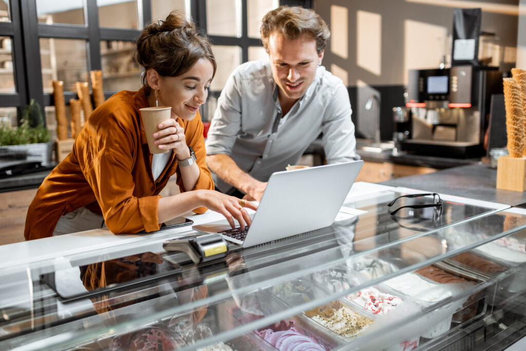 Man and woman use laptop to manage business